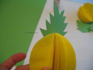 Blätter zwischen zwei gelben Ananasformen festkleben