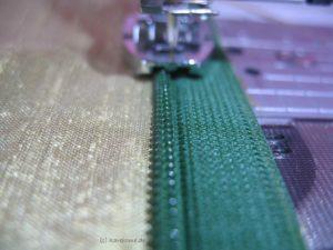 Die Nadel näht dicht neben den Reißverschlusszähnchen
